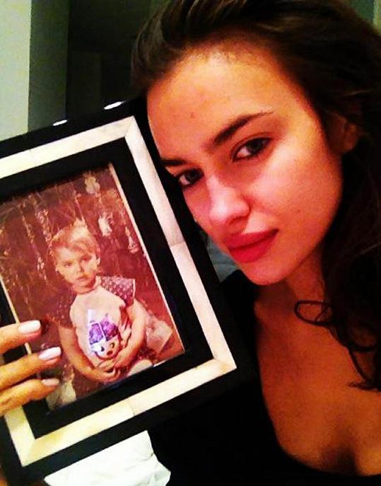 Nenalíčená Irina vedle své fotografie z dětství.