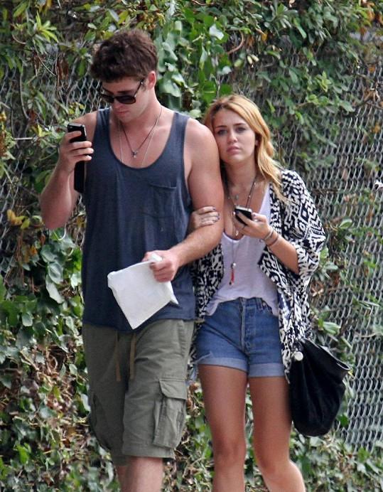 Miley se k Liamovi láskyplně tulí, on se soustředí na svůj mobil.