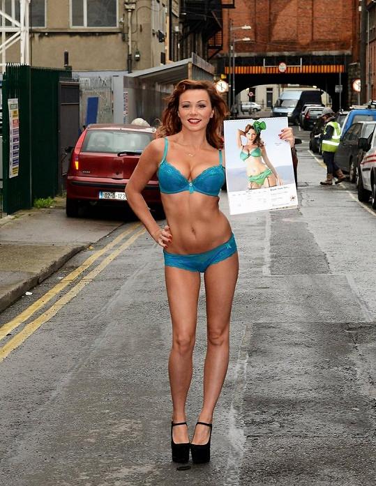 Krásná hnědovláska ukazuje svou fotografii v kalendáři.