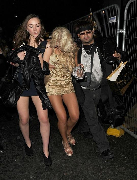 Dva lidé měli plné ruce práce, aby modelku udrželi na nohou.