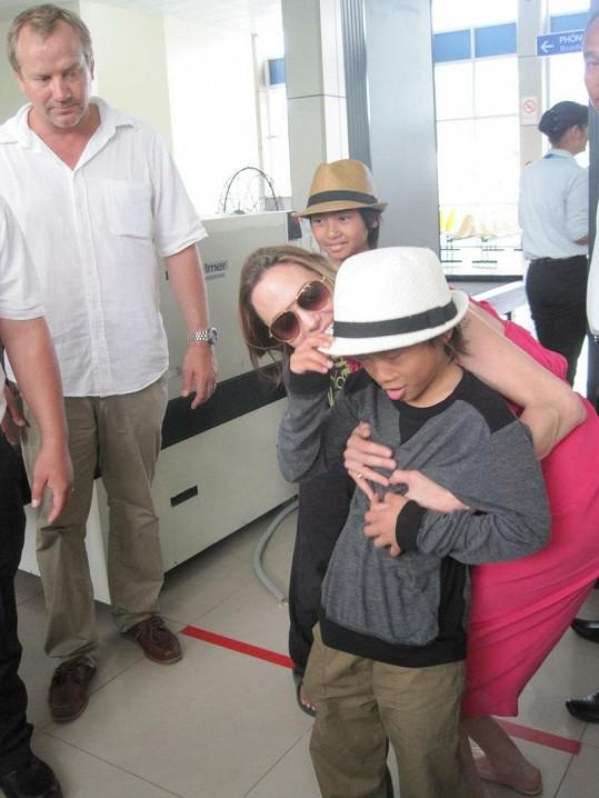 Angelina Jolie na vietnamském letišti nasazuje klobouk synkovi Paxu Thienovi. V pozadí jeho bratr Maddox.