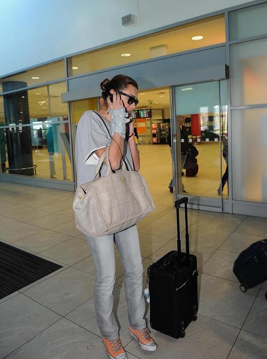 Alena si telefonicky domlouvá odvoz z letiště.