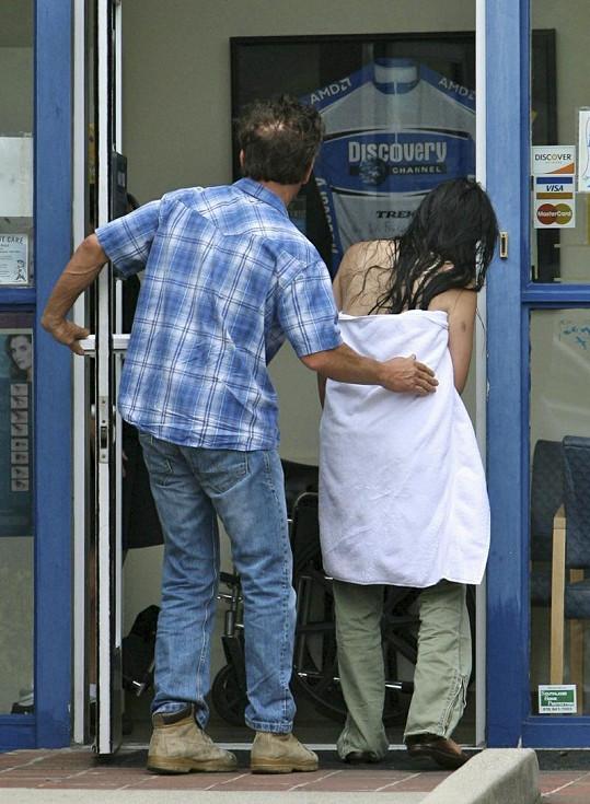 Herec zraněné asistentce pomáhá dojít k lékaři.
