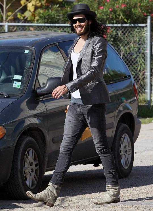 Vysmátý Russell Brand odchází z policejní stanice.