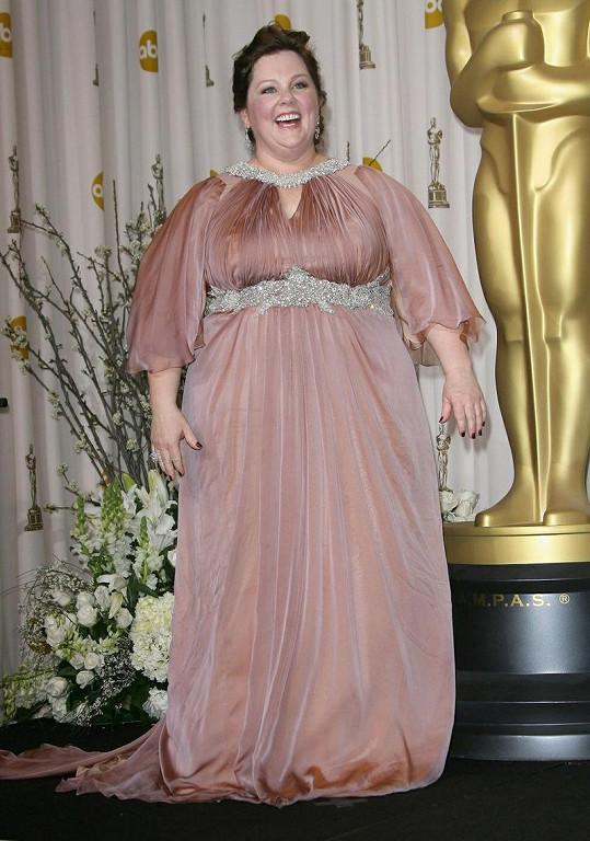 Ten, kdo doporučil prostorově výrazné herečce Melisse McCarthy, aby si oblékla tyto opticky rozšiřující šaty Marina Rinaldi, by si zasloužil trest smrti.