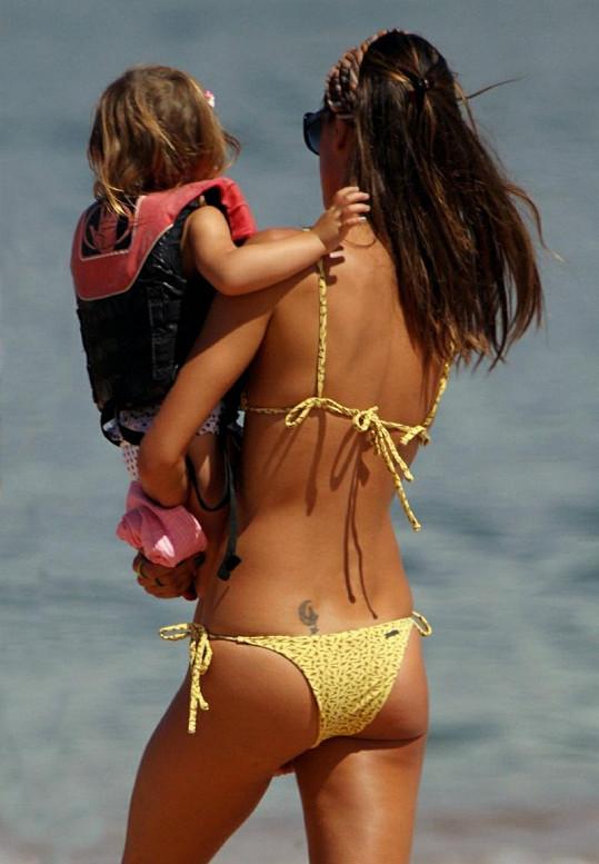 Topmodelka s dcerkou v náručí.