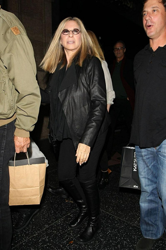 Americká zpěvačka a herečka odchází z restaurace v doprovodu manžela a přátel.