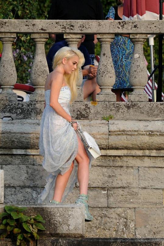 Lindsay v šedobílých dlouhých šatech a extravagantních krajkových botičkách.