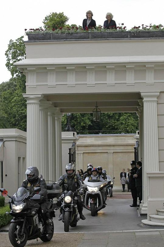 Motorkáři projíždějí okolo Charlesova sídla Clarence House. Z terasy přihlíží princova choť Camilla.