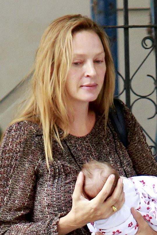 Herečka chodí po městě s dcerou v náručí.