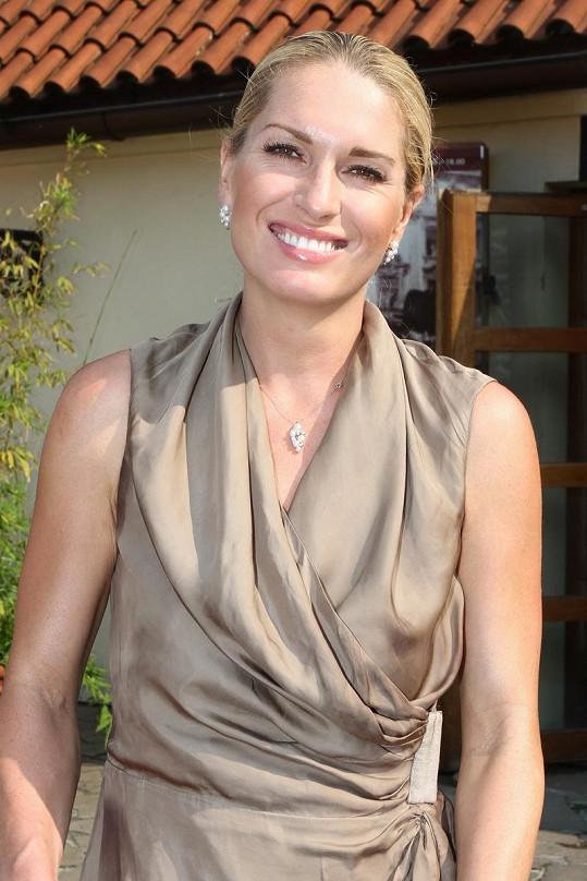 Olga Menzelová ve slušivých béžových šatech.