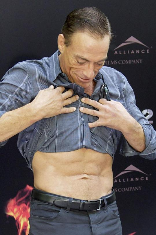 Jean-Claude se pyšně dívá na své v posilovně vydřené svalnaté břicho.