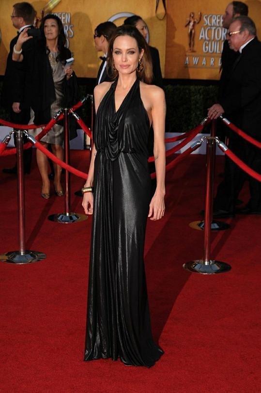 Angelina Jolie se nevymanila ze své oblíbené černé barvy a oblékla šaty z podzimní kolekce Jenny Packham v havraní barvě. Materiál a střih šatů zajímavě imitoval tekutinu v pohybu.