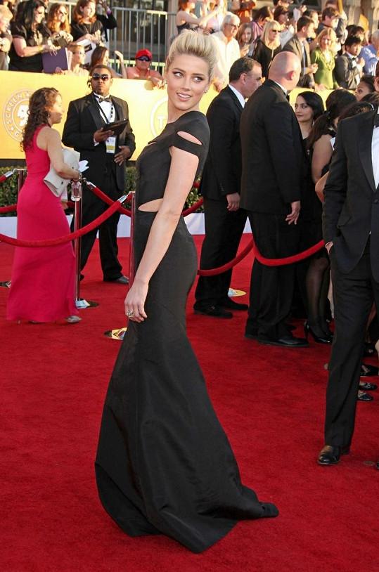 Róba od Zaca Posena působí díky použitému materiálu minimalisticky. Sílu šatům dodávají dráždivě umístěné prostřihy. Amber Heard v nich zabodovala i díky rozverně vyčesaným vlasům.