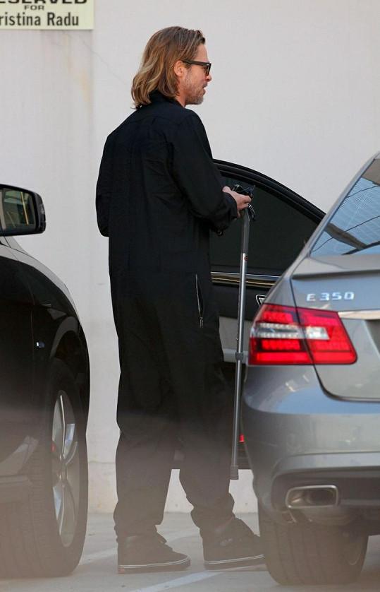 Brad Pitt nastupuje s hůlkou do auta.