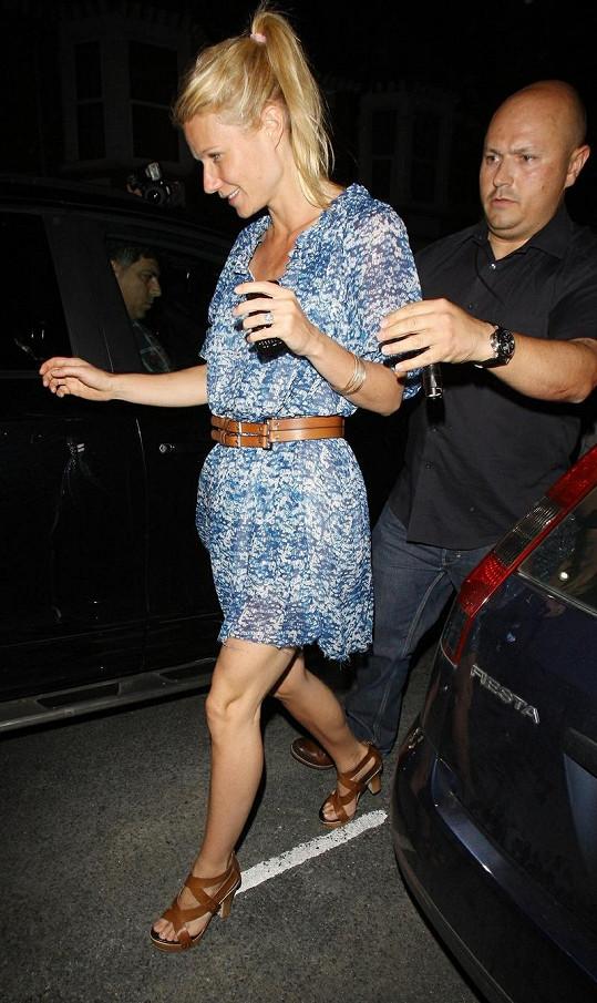 Muž starostlivě podpírá Gwyneth Paltrow, aby neupadla.