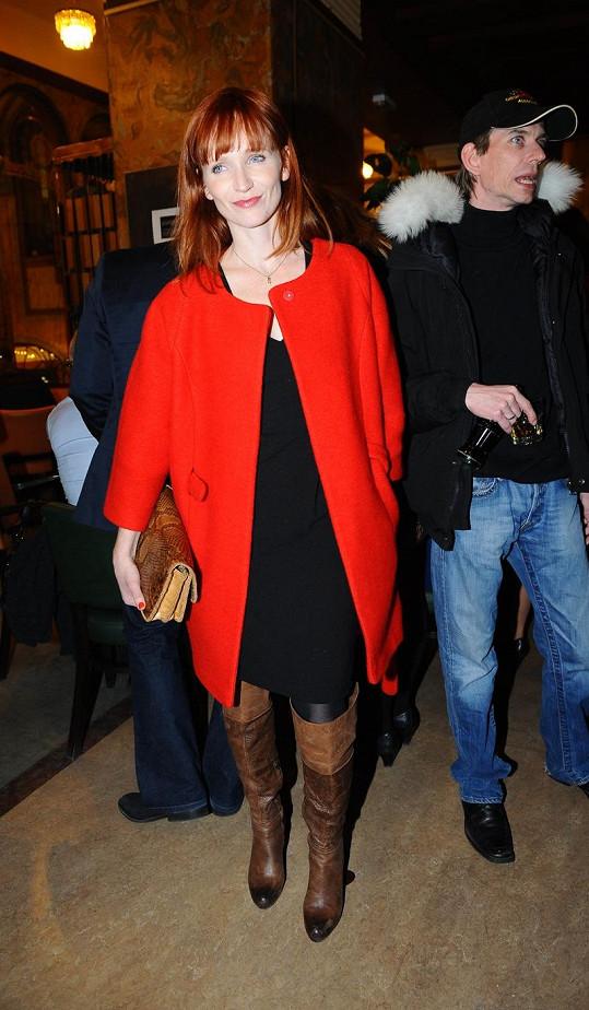 Aňa Geislerová v černých koktejlkách, rudém kabátku ve stylu šedesátých let a kabelce v imitaci hadí kůže od Pietro Filipi.