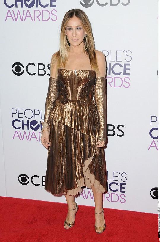 Bronzově metalický couture model od J. Mendela se dokonale snoubí s líčením Sarah Jessicy Parker. Proč ale představitelka Carrie ze Sexu ve městě opět oblékla i rukávy? Nepoučila se snad na Zlatých glóbech?