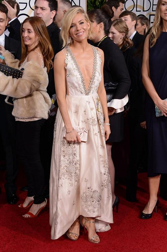 Sienna Miller měla v modelu od Miu Miu největší výstřih večera. Díky střihu šatů vynikly šperky Tiffany & Co., konkrétně platinové náušnice s diamanty, náramky a prsten se žlutým diamantem.
