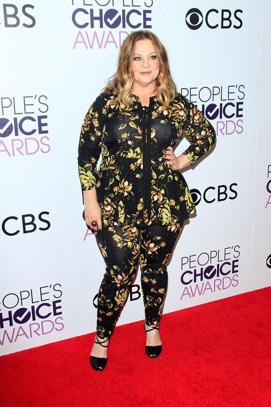 Vzhledem k tomu, že Melissa McCarthy zvolila místo modelu s dlouhou sukní kalhotový komplet s květinovým vzorem, svou postavu tak vhodně opticky odlehčila.
