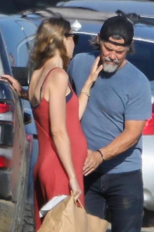 Josh hladí svou manželku po bříšku na pláži v Kalifornii.