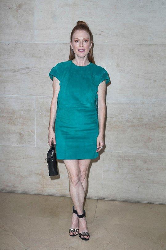 Na přehlídce ukázala nohy v krátkých zelených šatech.