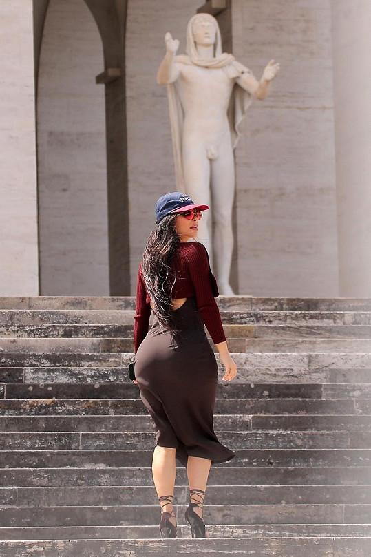 Šaty dokonale obepínaly její pověstné křivky.
