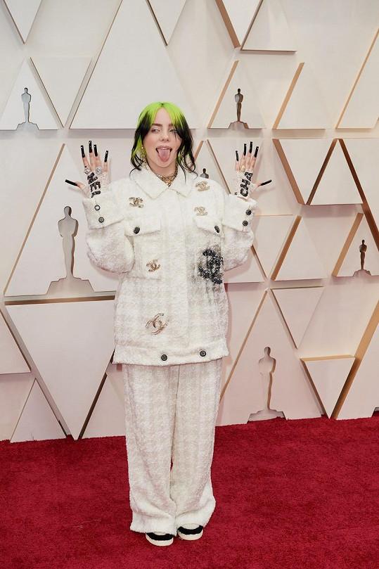 Billie Eilish se záměrně snaží upozadit svou ženskost. Po variacích na LV a Gucci přišel na řadu model od Chanela připomínající svým střihem pyžamo. Klasický tvídový kostým navržený Coco Chanel má ve svém šatníku každá bohatá babička.