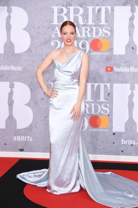 Šaty ve stylu dvacátých let ze stříbrného saténového hedvábí opticky prodlužovaly také Jess Glynne. Zásluhu na tom měla délka sukně až k zemi i vlečka.