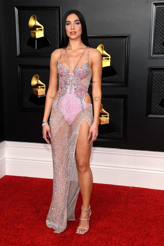"""Velmi silný look z ateliéru Versace. Dua Lipa v na míru ušitém modelu v duchu """"oblečená/neoblečená"""", připomínala zejména svým vlasovým stylingem zpěvačku Cher v jejím zlatém období."""
