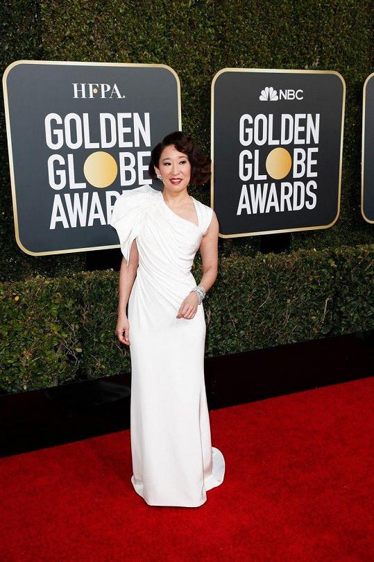 První šaty, které moderátorka večera Sandra Oh včera večer oblékla, byly rozhodně nejzdařilejší. Díky asymetrickému řešení sněhobílého modelu z ateliéru Versace vynikl výrazný náramek s diamanty.