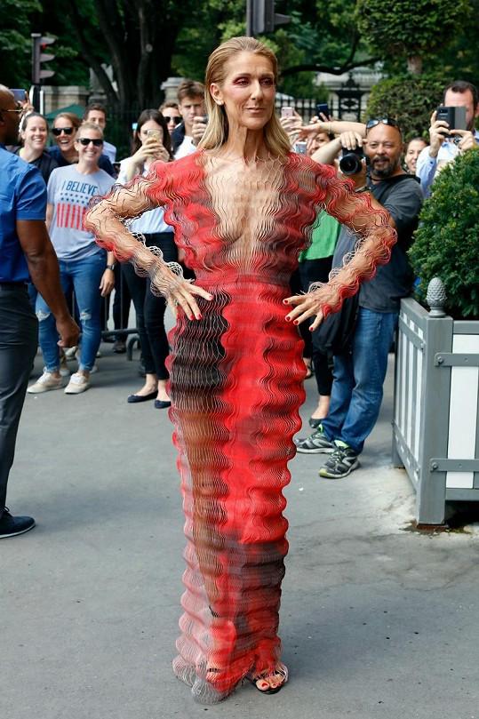 Zvlněné šaty její štíhlé postavě také moc nelichotily.