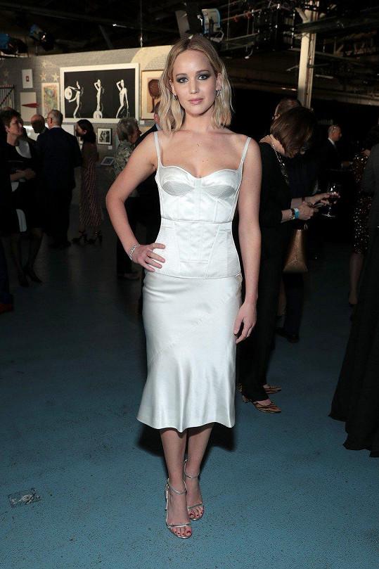 Herečka oblékla bílé hedvábné šaty.