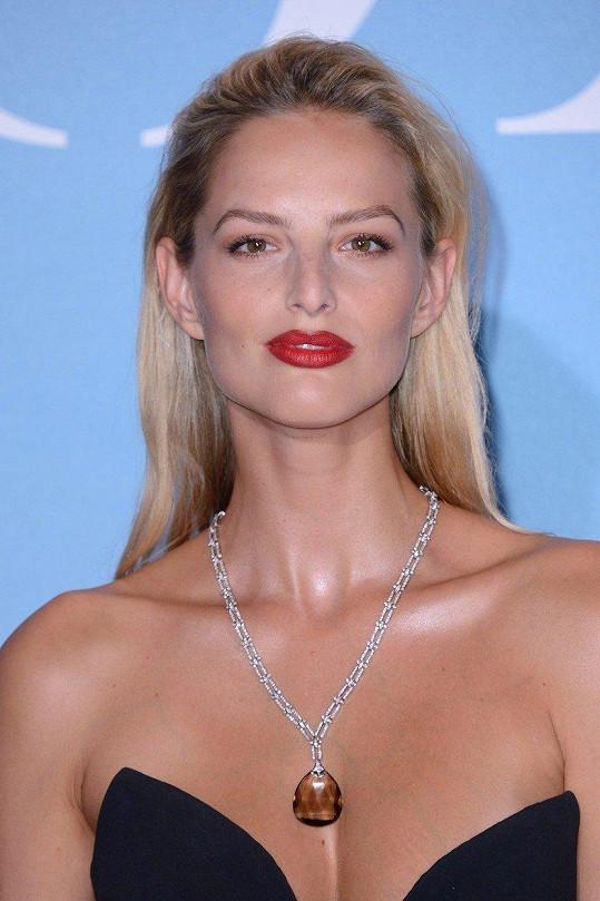 K přiléhavým černým šatům zvolila modelka výrazné večerní líčení a šperky Fruzsina Keehn.