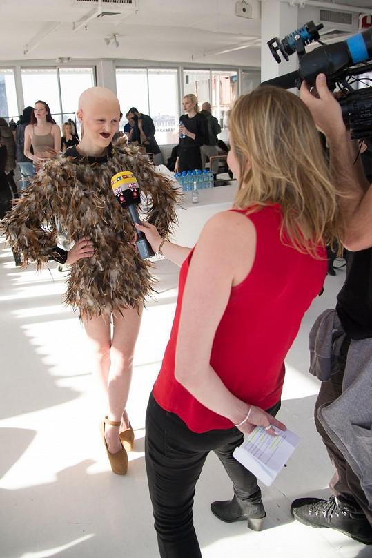 Gaydos v zákulisí módní přehlídky při poskytování rozhovoru.