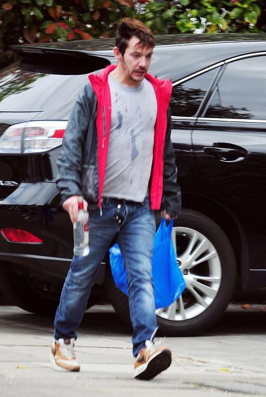 Ve flekatém triku a džínách s rozepnutým poklopcem vypadal jako bezdomovec.
