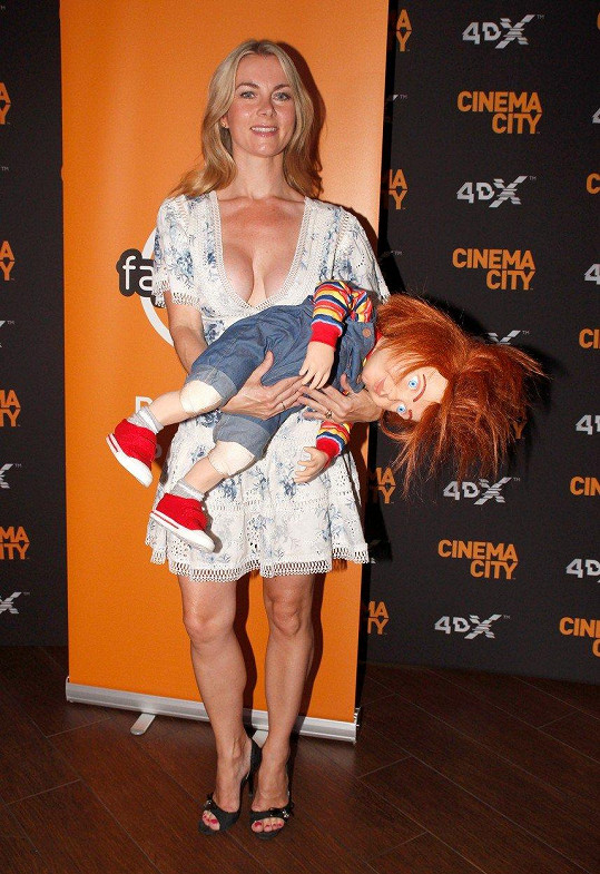 Bývalá rosnička pózující s panenkou Chucky