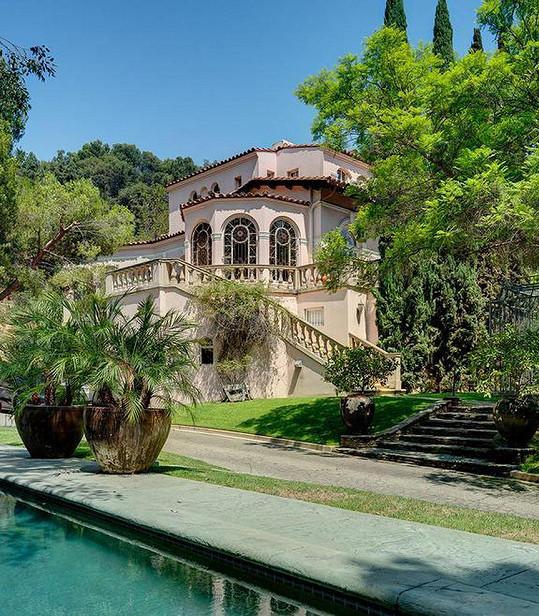 Dům je obklopený vzrostlou zelení, nechybí bazén.