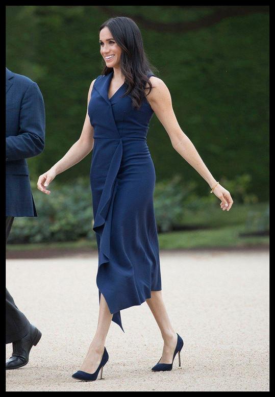 V šatech v barvě námořnické modři se Meghan rýsoval těhotenský pupík.