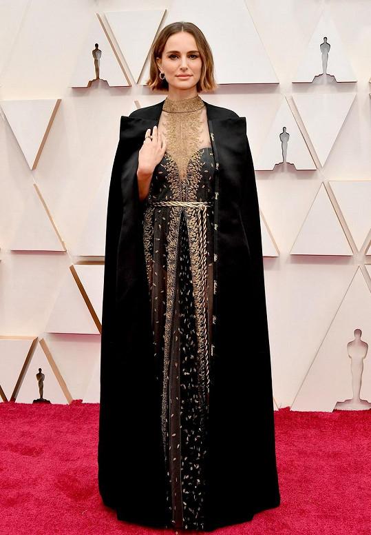 Natalie Portman přehodila přes zlatem vyšívanou róbu Dior kabát Maria Grazia Chiuri zdobený jmény ženských režisérek, které Akademie opomenula.