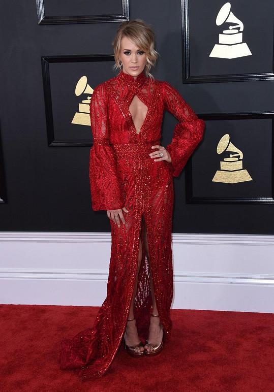 Šarlatové šaty Elie Madi s orientálním stojáčkem sice zahalovaly božské tělo Carrie Underwood od zápěstí po kotníky, štěrbina namísto výstřihu a rozparek sukně ale byly dostatečnými podněty k rozvoji divákovy představivosti.