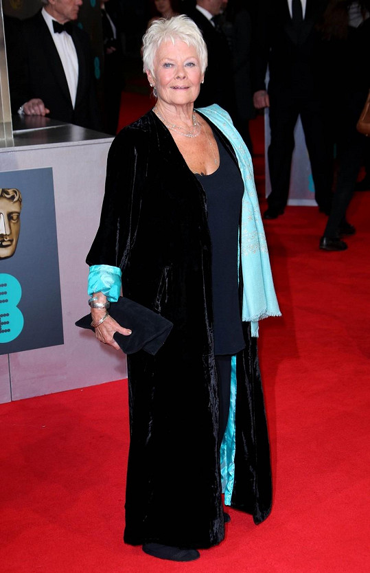 Za rok oslaví Judi Dench osmdesátku, a tak z taktických důvodů nesáhla po klasické velké večerní, ale oblékla temně modrý komplet, přes který přehodila sametový kabát. Tmavý celek rozzářila šálou a odhalenou podšívkou svrchníku.
