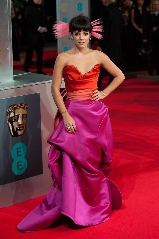 Od drzé zpěvačky Lily Allen nemůžeme čekat nudnou klasiku. Oranžovo-růžová kombinace na jejích šatech od Vivienne Westwood je divoká, toto spojení ale funguje.