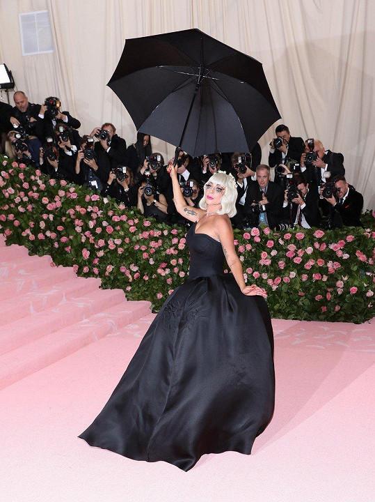 Na růžový koberec Lady Gaga nakráčela ve fusitovém oversize modelu, který velmi rychle svlékla, aby předvedla elegantní černé šaty bez ramínek s krinolínou.
