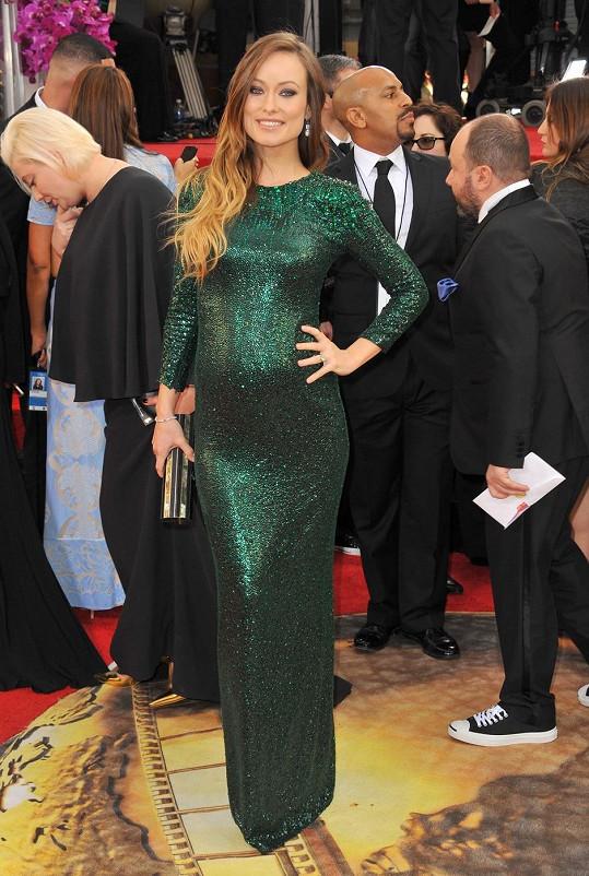 """Smaragdové přiléhavé šaty Gucci Premiére sladila těhotná hvězda s psaníčkem Emm Kuo a obutím Charlotte Olympia. Vlasy zesvětlené """"ombré"""" technikou si nechala volně rozpuštěné a zvolila decentní make-up."""