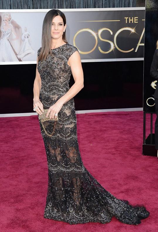 Sandru Bullock oblékl na Oscary návrhář Elie Saab do šatů seskládaných z krajkových palet zdobených korálky. Herečka model doplnila vintage psaníčkem Swarovski.