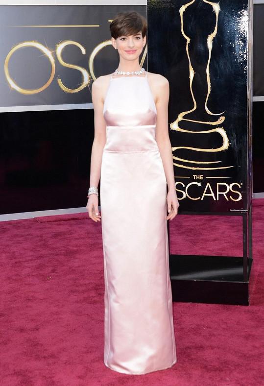 Zdá se, že sloupcovité růžové šaty Prada vystihují přesně ten styl, ve kterém se Anne Hathaway, nominovaná za vedlejší ženský herecký výkon, cítí nejlépe.