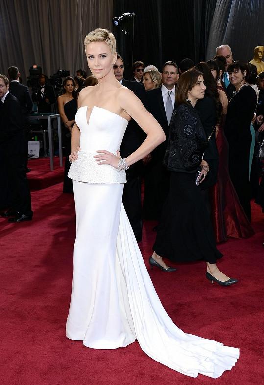 """Jak jinak. Tvář parfému J'Adore Charlize Theron se oblékla na Oscary v módním domě Dior. Zaujaly vás více sněhobílé šaty díky svému trendy """"peplum"""" volánu nebo slušivý krátký sestřih herečky?"""