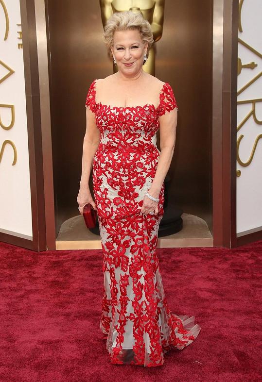 Jako by na sobě Bette Midler odřážela rudou barvu běhounu, když oblékla šaty z podzimní kolekce Reem Acra. Tento model s kaleidoskopově loženým rokokovým vzorem vzbuzoval u některých módních kritiků rozpaky, nám se ale Bette v těchto šatech libí.