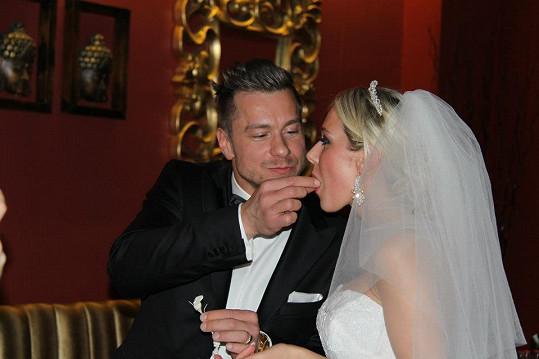 Vzájemné krmení novomanželů během slavnostní hostiny.